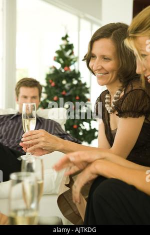 Zwei Frauen und ein Mann sitzen auf Sofas, trinken Champagner, Weihnachtsbaum im Hintergrund - Stockfoto