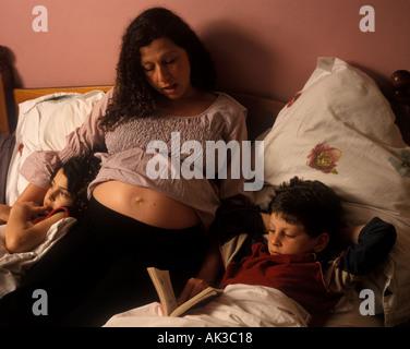 Eine schwangere Mutter liest zu ihrem Sohn und ihrer Tochter im Bett, London, UK. - Stockfoto