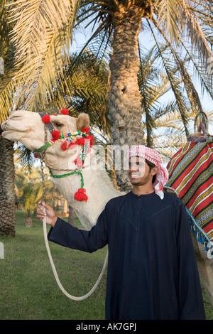 Lächelnden jungen arabischen Kamel Fahrer dekoriert mit arabischen Kamel in der Außenanlage, Verkauf von Kamelreiten, - Stockfoto