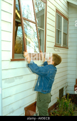 18 Jahre alt Teen Elternhaus Storm Windows aufsetzen. St Paul Minnesota USA - Stockfoto