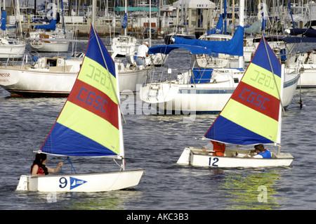 Zwei kleine Segelboote mit festgemachten Boote im Hintergrund - Stockfoto