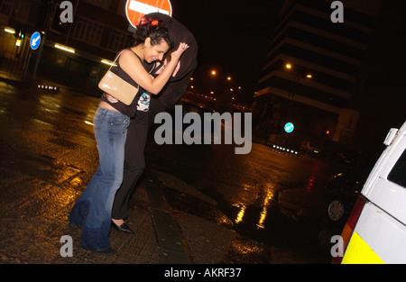 Junge Menschen in einer Nacht finden ihren Weg zu einem Pub oder Club durch Wind und Regen Cardiff South Wales UK - Stockfoto