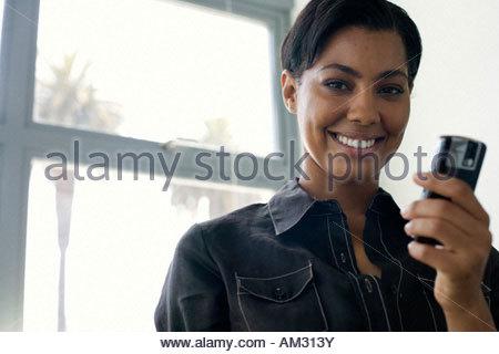 Geschäftsfrau hält Handy im Büro - Stockfoto