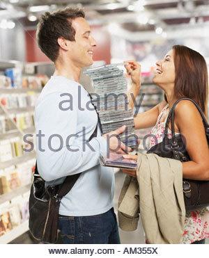 Mann, der Stapel von CDs mit Frau indem man mehr an der Spitze - Stockfoto