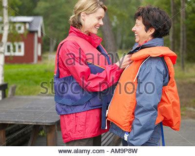 Frau helfen, eine andere Frau mit ihrer Rettungsweste Lächeln auf den Lippen. - Stockfoto