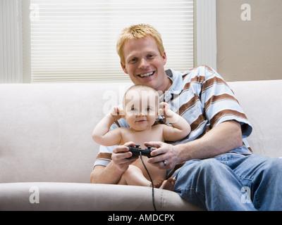 Mann und Baby auf Sofas mit Videospiel-Controller lächelnd - Stockfoto