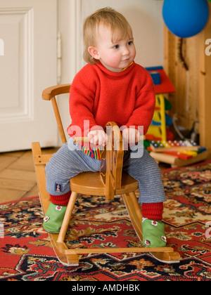 kleines Kind Mädchen im Alter von einem Jahr auf Schaukelpferd Stuhl sitzend - Stockfoto