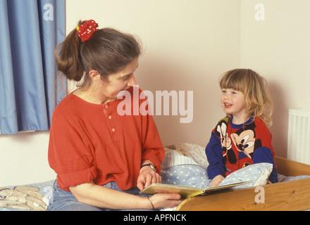 Mutter und Kleinkind, einem guten Buch vor dem Schlafengehen zusammen - Stockfoto