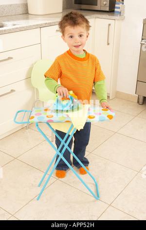 ein Junge spielt in einer Küche mit einem Spielzeug Bügeln set - Stockfoto