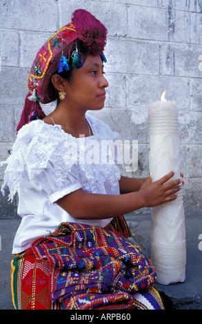 Junge Frau in Tracht von San Sebastian Retalhuleu Guatemala hält eine große Kerze Fiesta feiern - Stockfoto