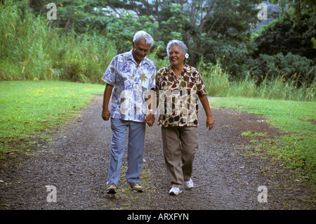 Liebevolle senior Hawaiian Mann und Teil-Hawaiian Frau einen Park Weg zu Fuß und Hand in Hand; Hoomaluhia botanischen - Stockfoto