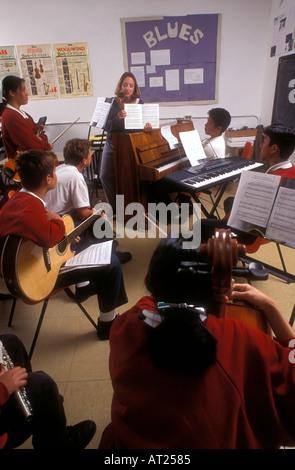Gemischtrassigen Gruppe von Jugendlichen Studenten spielen verschiedene Instrumente im Musikunterricht mit Musikbücher - Stockfoto