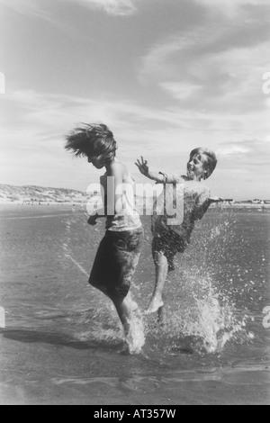 Ein Junge und ein Mädchen zusammen im Meer planschen - Stockfoto
