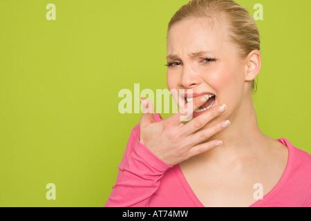 Frau fühlt ihr Zahn mit ihrem finger, Porträt - Stockfoto
