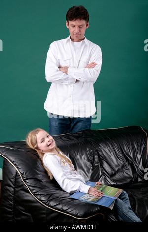 Tochter sitzen auf der Couch mit einem Buch mit ihrem Vater auf - Stockfoto