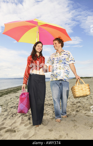 Paar am Strand entlang schlendern - Stockfoto