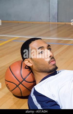 Ein junger Mann legt seinen Kopf auf einen basketball - Stockfoto