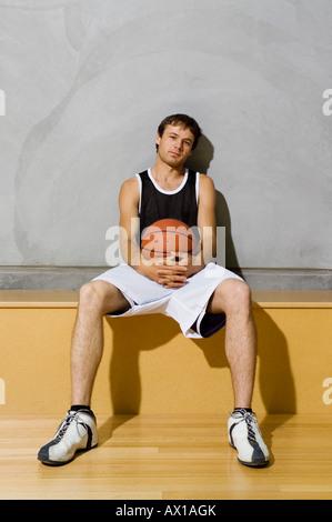 Ein junger Mann sitzt auf einer Bank auf einem Basketballfeld - Stockfoto