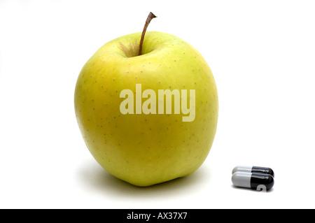 Apple und Pillen auf weißem Hintergrund - Stockfoto