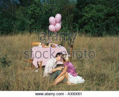 Paar küssen durch einen Tisch in einem Feld - Stockfoto