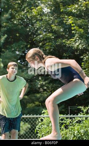 Kaukasische Mädchen vorbereiten, ein Sprungbrett rückwärts zu gehen.  Sie wird von ihrem Bruder beobachtet. - Stockfoto