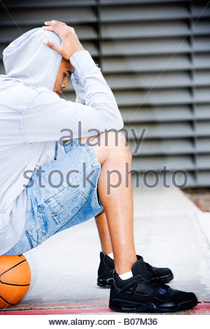 Porträt eines jungen afrikanischen amerikanischen Mannes in einem grauen Kapuzenshirt sitzt auf einem Basketball, - Stockfoto