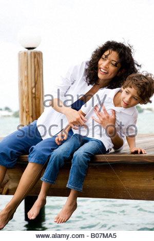 Mutter und Sohn sitzen auf Steg Flickschusterei - Stockfoto