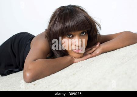 Junge, dunkelhäutige Frau trug ein schwarzes Kleid, liegend auf einem hellen Teppich - Stockfoto