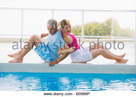 Älteres paar Rücken an Rücken sitzen am Rand des Schwimmbad, lachen - Stockfoto