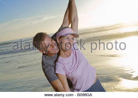 Älteres paar Lachen und Spaß am Strand bei Sonnenuntergang - Stockfoto