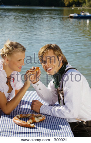 Junges Paar in der traditionellen bayerischen Outfit, Essen Prezel, München - Stockfoto