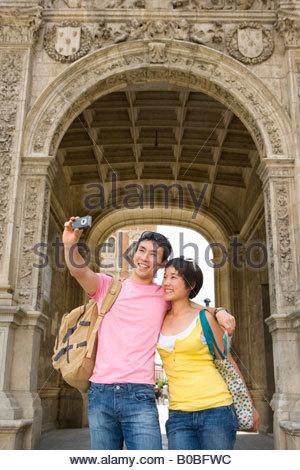 Paar nehmen Foto von sich selbst durch Torbogen, smiling, niedrigen Winkel Ansicht - Stockfoto