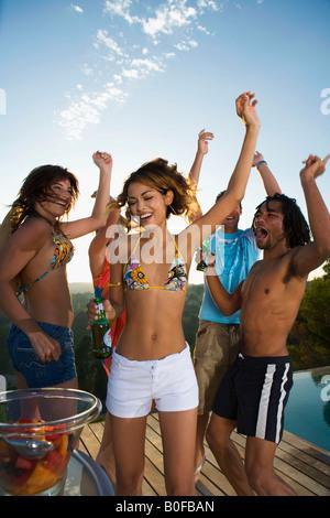 Junge Leute tanzen auf Terrasse, Pool - Stockfoto