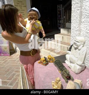 Mutter hielt Buddha Maske vor Kleinkindes Gesicht während des Einkaufs für kunstgewerbliche Gegenstände, Mijas Pueblo, - Stockfoto