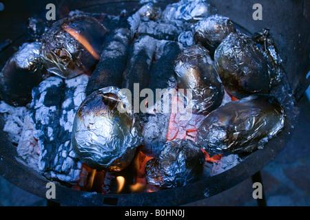 Gebackene Kartoffeln eingewickelt in Alufolie Backen auf heißen Kohlen, BBQ - Stockfoto