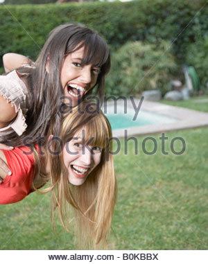 Frau im Freien geben andere Frau Huckepack-Fahrt und lächelnd - Stockfoto