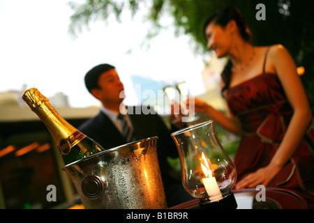 """Sektflöte """"Soirée"""" und Eisbehälter, paar trinken im Hintergrund - Stockfoto"""