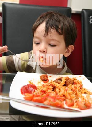2 Jahre alter Junge sitzt am Tisch beim Abendessen - Stockfoto