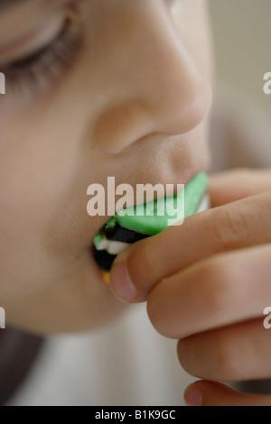 Im Alter von sechs junge isst Lakritz Allsort candy - Stockfoto