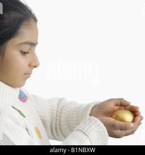 Seitenansicht eines Mädchens hält ein Easter egg - Stockfoto