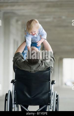 Mann im Rollstuhl mit Baby spielen - Stockfoto