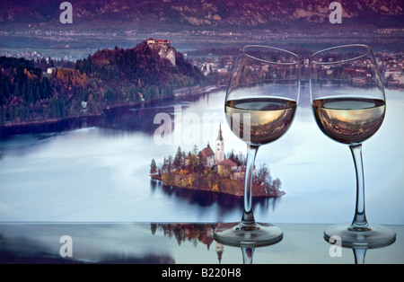 Zwei Weißweingläser zuneigen einander mit der Insel und der Kirche am Bleder See bei Sonnenuntergang Slowenien Osteuropa - Stockfoto