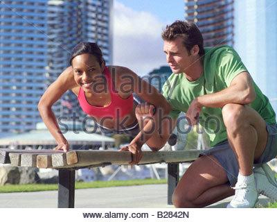Männlichen Fitness Instruktor Ausbildung Frau auf der Bank im Freien, Lächeln, Porträt der Frau - Stockfoto