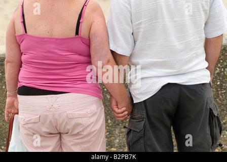 Gewöhnliche Übergewicht mittleren gealterten paar Hand in Hand im Urlaub Wales UK Rückansicht - Stockfoto