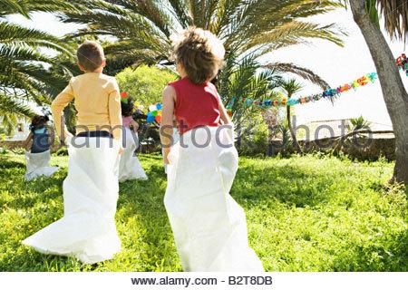 Kinder laufen Sackhüpfen auf Geburtstagsparty - Stockfoto