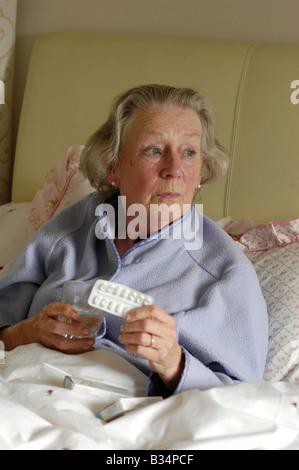 alte Dame im Bett mit Pillen, die betroffenen suchen - Stockfoto