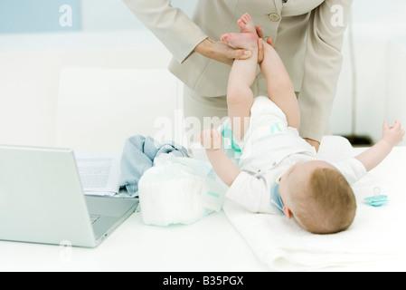 Berufstätige Frau wechselnden Babywindel auf Schreibtisch, beschnitten Ansicht - Stockfoto