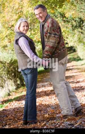 Paar im freien Weg im Park Hand in Hand und lächelt (Tiefenschärfe) - Stockfoto