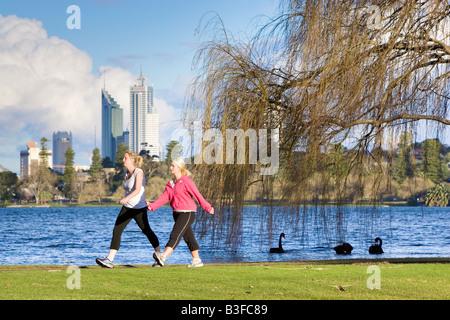 Zwei Frauen trainieren in einem Park mit Wolkenkratzern in der Ferne. Lake Monger, Perth, Western Australia, Australia - Stockfoto