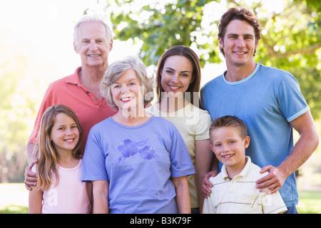 Großfamilie stehen im Park lächelnd - Stockfoto